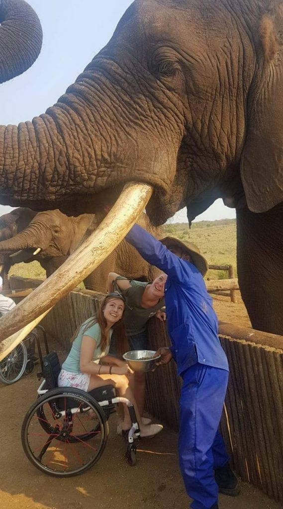 Wheelchair user enjoys feeding elephants